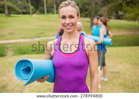 Happy athletic group holding mat on a sunny day - stock photo
