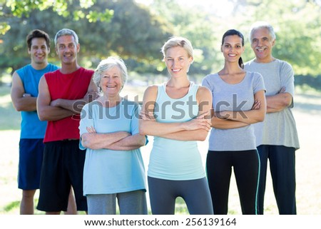 Happy athletic group smiling at camera with hands crossed on a sunny day - stock photo