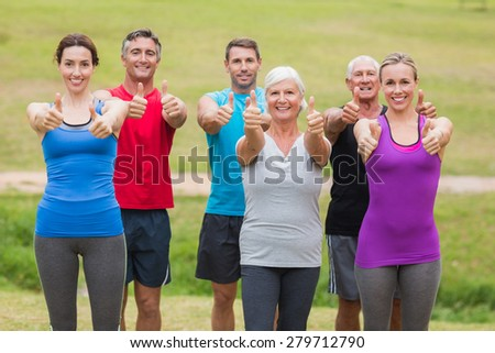 Happy athletic group smiling at camera with thumbs up on a sunny day - stock photo