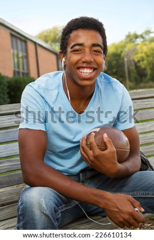 Happy athletic student  holding a football and listing to music. - stock photo
