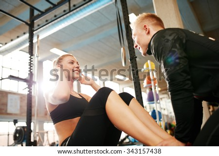 Happy athletic woman doing curl up exercise at the gym with the help of her personal trainer. Fitness female doing sit ups with man holding her feet. - stock photo