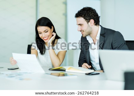 Happy atmosphere between a businesswoman and a businessman in a tidy, white office - stock photo