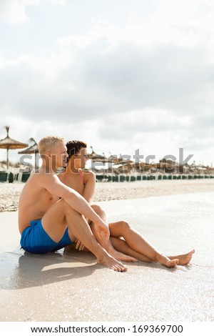 Happy attractive affectionate young couple sunbathing together on the beach in their swimwear while enjoying a tropical summer holiday during the annual vacation - stock photo