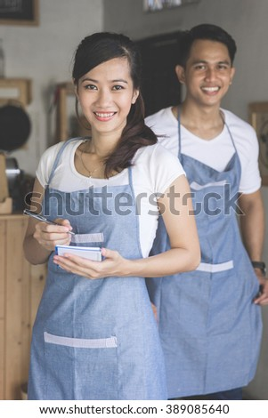 Happy attractive asian female waiter in apron writing order and looking at camera. her partner at the background - stock photo