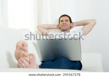 happy attractive Brazilian man freelance working with computer laptop laying on couch at home relaxed thinking and dreaming of future successful work project