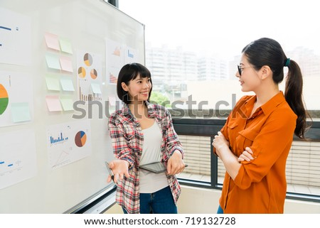 happy attractive business woman holding mobile pad standing in front of whiteboard and talking with company cooperation manager.