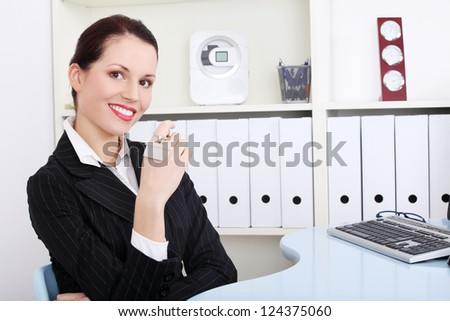 Happy attractive businesswoman at the office holding house keys. Real estate agent.