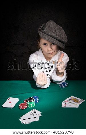 Happy attractive child girl holding the winning combination of poker cards