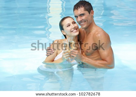 Happy attractive couple celebrating with champagne in swimming pool - stock photo