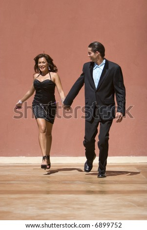 Happy attractive couple holding hands and running