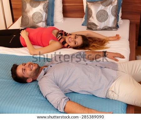 Happy attractive couple lying in bed, smiling head to head. - stock photo