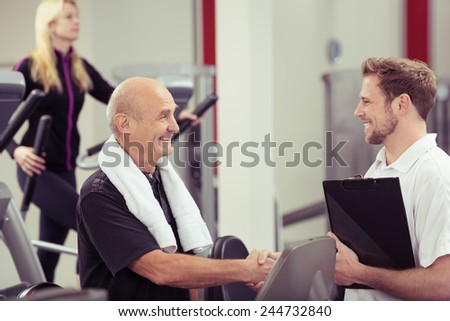 Happy attractive elderly man shaking hands with a trainer at the gym as he does his weekly exercises in a healthy and fitness concept - stock photo