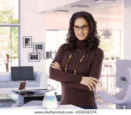 Happy attractive female casual caucasian interior designer at trendy luxury home, wearing glasses, standing arms crossed, looking at camera, smiling. - stock photo