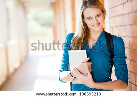 happy attractive female university student with tablet computer on campus - stock photo