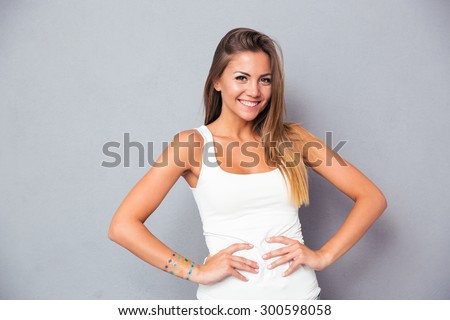 Happy attractive girl standing over gray background and looking at camera - stock photo