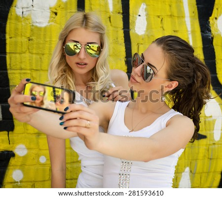 Happy attractive girls with smart phone take selfie against urban grunge graffiti wall. - stock photo