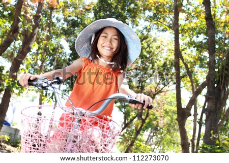 happy attractive litte girl riding bicycle outdoor