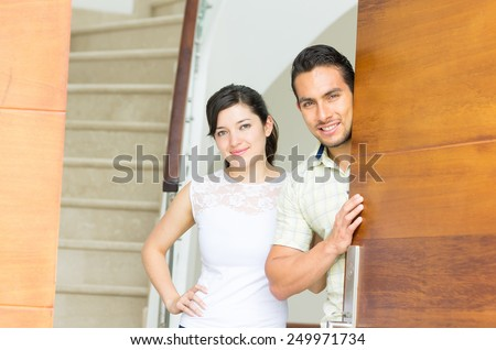 happy attractive loving couple opening the door to their new house - stock photo