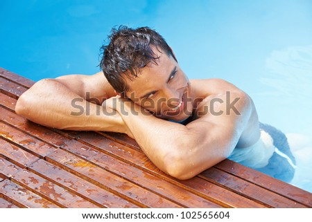 Happy attractive man leaning at edge of swimming pool - stock photo