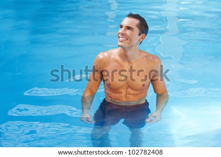 Happy attractive man standing in blue water in a swimming pool - stock photo