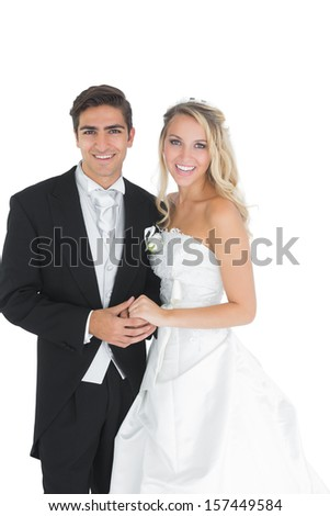 Happy attractive married couple posing holding hands smiling at camera - stock photo