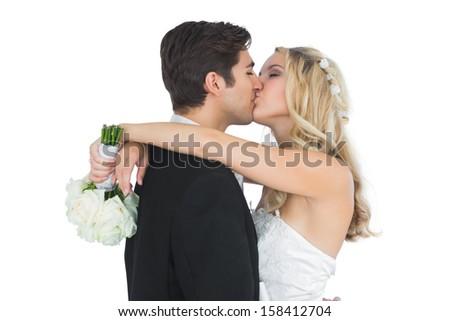Happy attractive married couple posing kissing each other holding a bouquet - stock photo