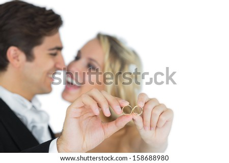 Happy attractive married couple showing their wedding rings looking at each other  - stock photo