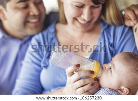 Happy Attractive Mixed Race Couple Bottle Feeding Their Son. - stock photo