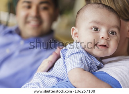Happy Attractive Mixed Race Couple Burping Their Smiling Son. - stock photo