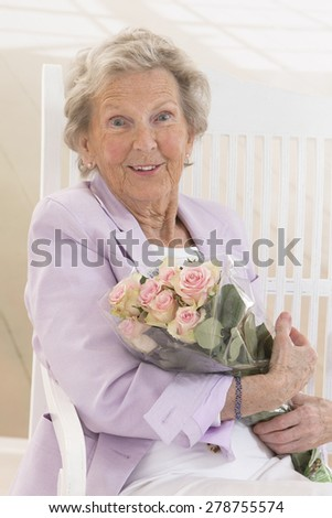 Happy attractive senior woman with a bunch of flowers - stock photo