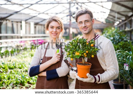 Happy attractive woman and man gardeners holding small mandarine tree and tools for plants transplsntation in garden center - stock photo