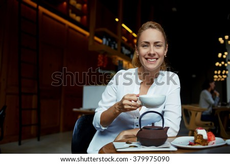 Happy attractive woman holding cup of tea and smiling to the camera while sitting in modern cafe-bar interior, cheerful female posing with cup of coffee in hand while relax in comfortable restaurant  - stock photo