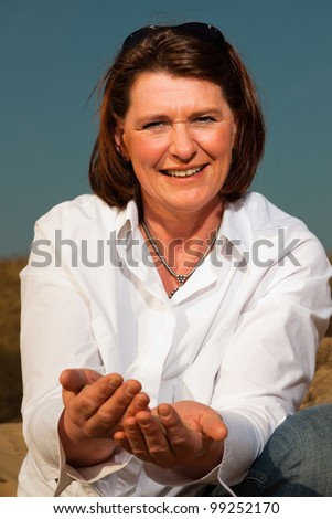 Happy attractive woman middle aged enjoying outdoors playing with sand. Clear sunny spring day with blue sky. - stock photo
