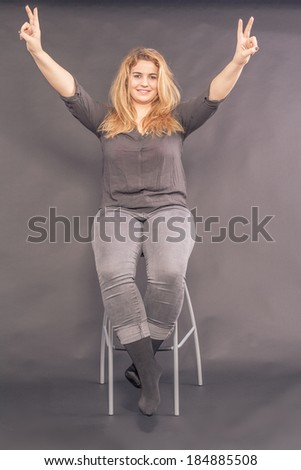 Happy attractive woman sitting on a stool making a V-sign with both her hands for peace or victory as she smiles at the camera / Happy attractive woman making a V-sign - stock photo