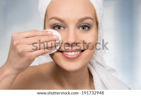 Happy attractive women removing makeup in the bathroom - stock photo