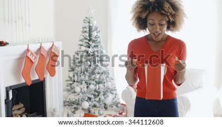 Happy attractive young African woman opening Christmas gifts in front of the tree looking into a gift bag in surprise