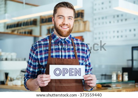 Happy attractive young barista in plaid shirt and brown apron holding open sign at the coffee shop - stock photo