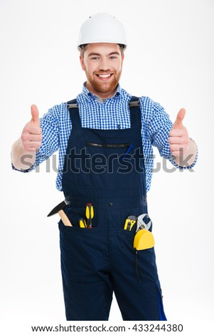 Happy attractive young builser in helmet showing thumbs up with both hands - stock photo