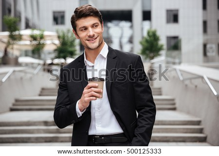 Happy attractive young businessman smiling and drinking coffee in the city