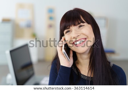 Happy attractive young businesswoman taking a phone call on her mobile grinning with pleasure as she listens to the conversation while standing alongside her desk in the office - stock photo