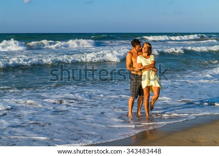 Happy attractive young couple in beachwear, enjoying a summer dusk at the beach, having fun walking barefoot, getting wet, kissing and teasing one another.