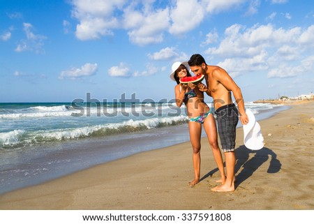 Happy attractive young couple in bikini and shorts enjoying a summer dusk at the beach, having fun walking barefoot, sharing a slice of watermelon,  and teasing one another. - stock photo