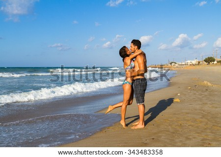 Happy attractive young couple in bikini and shorts enjoying summer dusk at the beach, practicing fitness exercises, having fun walking barefoot, kissing and teasing one another.