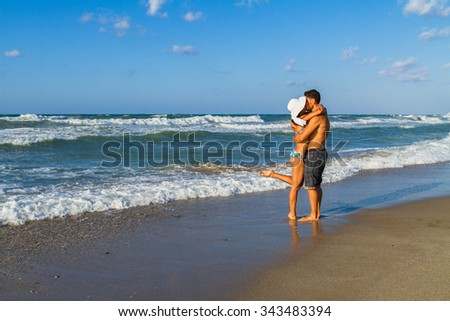 Happy attractive young couple in bikini and shorts enjoying summer dusk at the beach, practicing fitness exercises, having fun walking barefoot, kissing and teasing one another. - stock photo