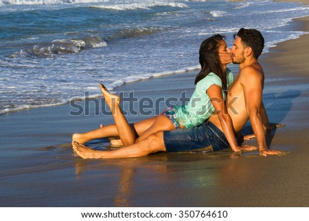 Happy attractive young couple in bikini and shorts enjoying summer dusk at the beach, practicing fitness exercises, having getting wet, kissing and teasing one another. - stock photo