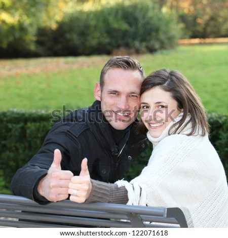Happy attractive young couple sitting on a wooden bench outdoors looking back at the camera giving a thumbs up to show their approval - stock photo