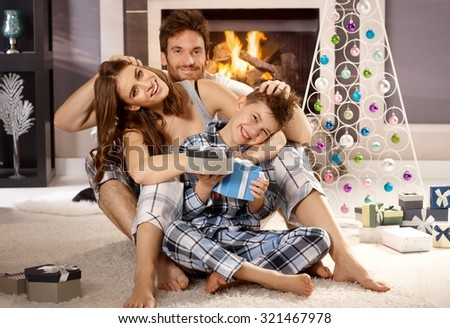 Happy attractive young family loving, hugging and having fun at christmas morning in pajamas on floor by christmas tree.
