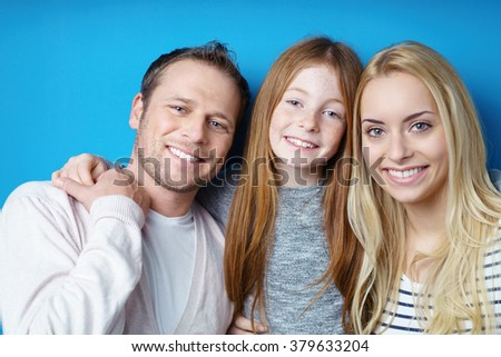 Happy attractive young family posing together with a pretty young redhead girl with a lovely smile flanked by her parents - stock photo