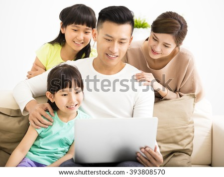 Happy Attractive Young  Family watching the laptop - stock photo