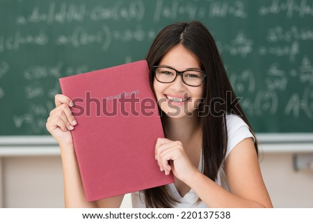 Happy attractive young female college student wearing glasses holding up a red file in her hands displaying it to the camera as she sits at her desk in class - stock photo